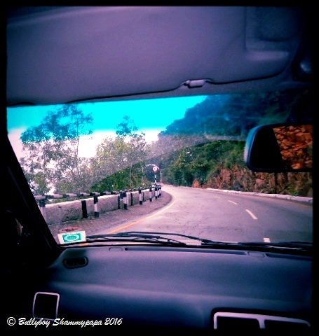 A view of a mountain road from inside a car